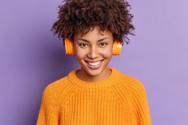 幸せな女性の音楽愛好家のクローズアップショットは、耳にワイヤレスステレオヘッドフォンを着用し、プレイリストの笑顔からお気に入りの曲を積極的に楽しんでいます