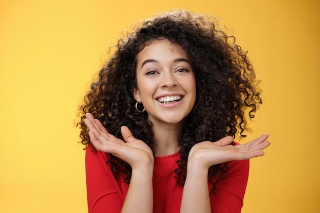 곱슬머리와 완벽한 피부를 가진 행복한 친절하고 예쁜 백인 여학생의 클로즈업 샷은 손바닥을 들고 기뻐하며 노란색 배경 위에서 즐거운 시간을 보내는 얼굴 근처에 펼쳐져 있습니다.