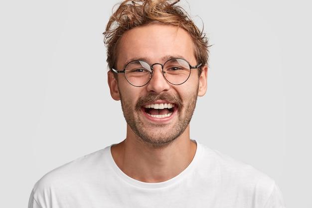 丸いメガネで幸せなスタイリッシュな男のショットをクローズアップ、顔に前向きな笑顔を持っている、給料を受け取ってうれしい、新しい購入にお金を使うつもり