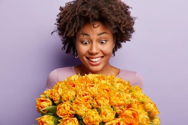 幸せな驚きの暗い肌の若い女性のクローズアップショットは、花の巨大な束を見つめ、このプレゼントが彼女のためのものであるとは信じられず、紫色の壁に隔離されています。うわー、なんて素敵なチューリップ!
