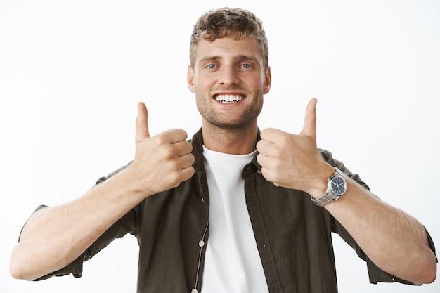 毛と青い目が親指を上げて笑顔で満足している好きな製品を見せて、灰色の壁の上でそれを使用することをお勧めする、幸せで喜んでいる魅力的なヨーロッパのブロンドの男性のクローズアップショット