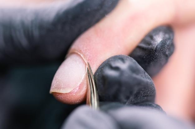 ビューティーサロンでのハードウェアマニキュアのクローズアップショット。ネイリストは電気爪やすりを適用しています