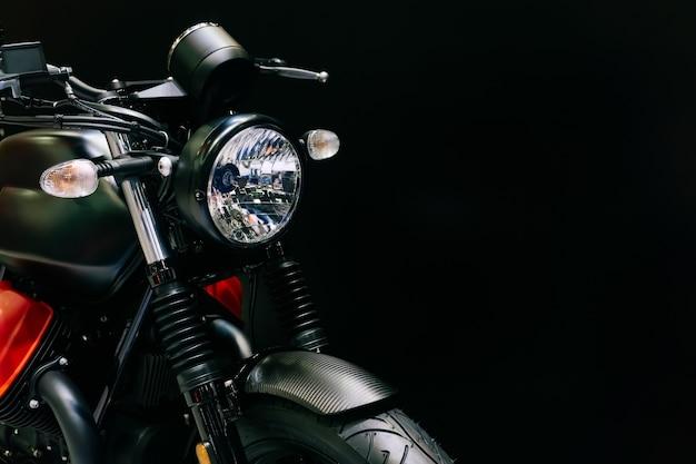 黒い背景に新しいモダンな黒いオートバイのヘッドライトのショットを閉じます