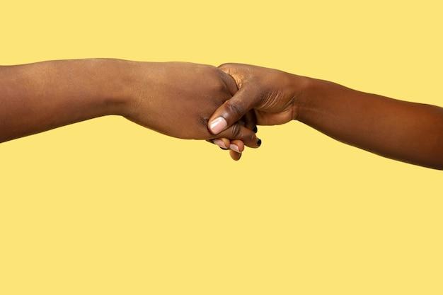 黄色の壁に分離された手を握って人間のショットを閉じます。人間関係、友情、パートナーシップ、家族の概念。コピースペース。