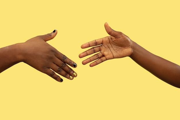 노란색에 고립 된 인간의 손을 잡고 총을 닫습니다