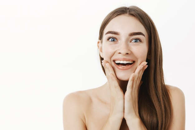 美容製品が皮膚に塗布された後、驚きの結果で満足している顔に手のひらを広く笑って感動して喜んでいる若い女性のクローズアップショット