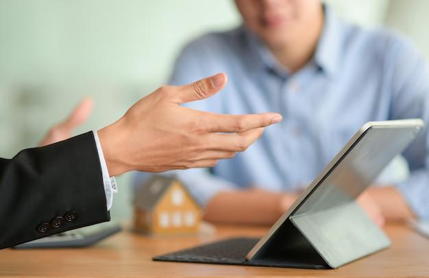 보험 중개인의 클로즈업 샷은 태블릿과 함께 건강 보험 프로그램을 소개합니다.
