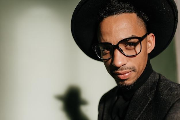 어두운 방에서 포즈를 취하는 안경에 관심이있는 남자의 클로즈업 샷. 회색 벽에 고립 된 유행 모자에 흑인 남성 모델의 초상화.