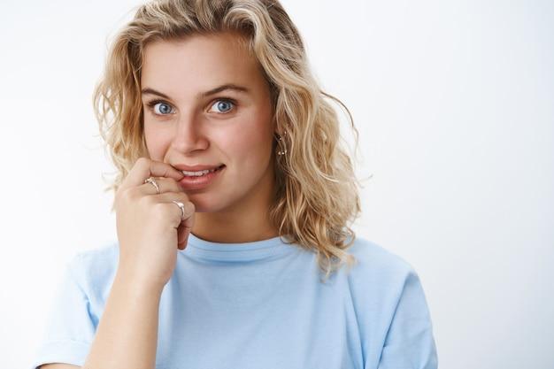 Крупным планом заинтригованная симпатичная европейская женщина с голубыми глазами и короткими светлыми волосами, с желанием и интересом смотрящая в камеру, улыбается и трогает губу, как если бы любопытно и хотела что-то попробовать