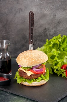 회색 표면에 줄기와 검은 트레이 소스 케첩 토마토에 맛있는 고기 샌드위치와 피망에 칼의 총을 닫습니다