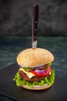 여유 공간이있는 고립 된 흐린 표면에 검은 쟁반에 맛있는 샌드위치에 칼의 총을 닫습니다
