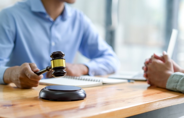 Крупным планом адвокат, держащий молоток, давая советы по закону, концепции справедливости.