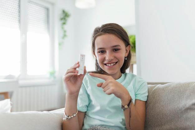 ネガティブテストデバイスを保持している少女のクローズアップショット。彼女の陰性コロナウイルスを示す幸せな少女-covid-19迅速検査。コロナウイルス