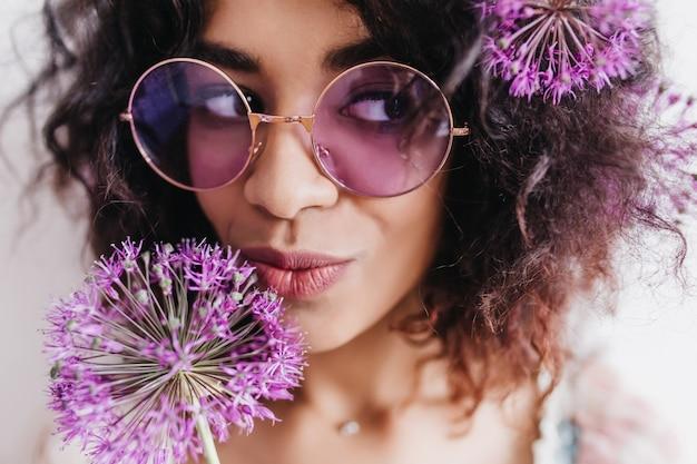 ふざけて目をそらしている愛らしい黒人少女のクローズアップショット。紫色の花でポーズをとる陽気な巻き毛の女性の肖像画。