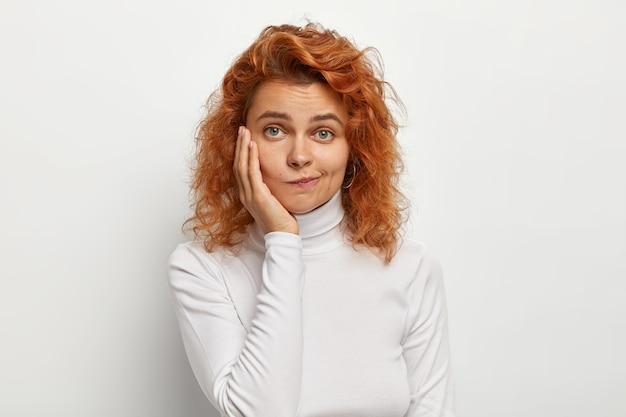 赤い巻き毛の素敵な女性のクローズアップショット、唇を財布に入れ、疑わしい表情で見え、頬に触れ、白い壁にポーズをとり、タートルネックのジャンパーを着ています。人間の表情