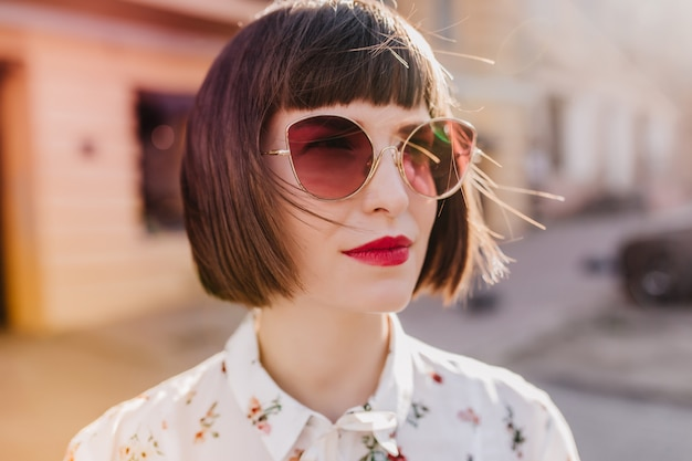 흰 블라우스에 웅장한 유럽 여자의 클로즈업 샷. 어두운 선글라스에 사랑스러운 여자의 야외 사진.