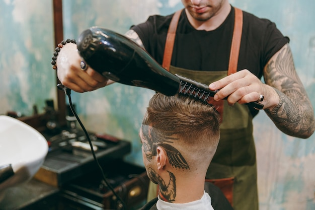 이발소에서 트렌디한 머리를 자르는 남자의 사진을 클로즈업하세요. 문신을 한 남성 헤어스타일리스트는 고객에게 서비스를 제공하고 헤어드라이어로 머리를 말립니다.