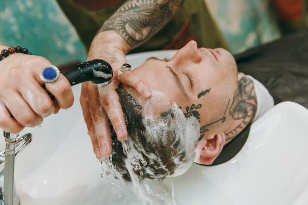 이발소에서 트렌디한 머리를 자르는 남자의 사진을 클로즈업하세요. 고객에게 봉사하는 문신의 남성 미용사, 머리를 씻는 것