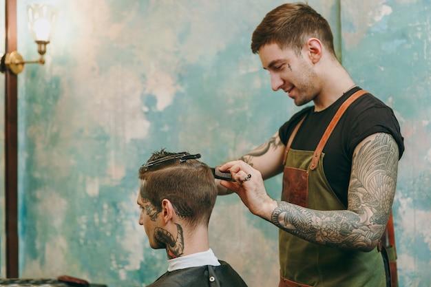 理髪店で流行の散髪をしている男性のクローズアップショット。クライアントにサービスを提供する入れ墨の男性のヘアスタイリスト。