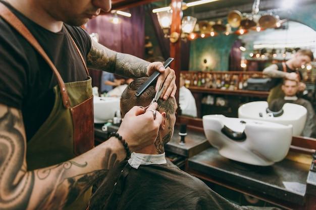 이발소에서 트렌디한 머리를 자르는 남자의 사진을 클로즈업하세요. 고객에게 봉사하는 문신의 남성 미용사.