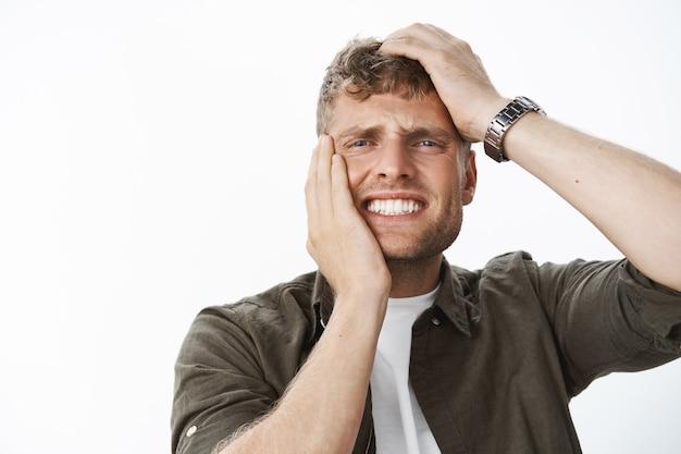 Крупным планом - мужчина в агонии и печали, испытывающий тревогу и беспокойство, держится за руки за голову и лицо, стиснув зубы от болезненного чувства сожаления и разочарования, гримасничающего над серой стеной