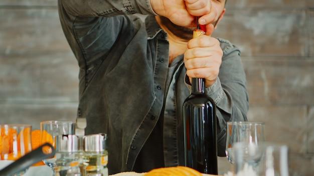 昼食時に彼の家族のために赤ワインのボトルを開く男のショットをクローズアップ。