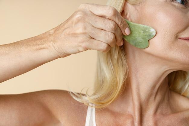 Снимок крупным планом зрелой блондинки с идеальной сияющей кожей, использующей инструмент для массажа нефрита гуа ша для