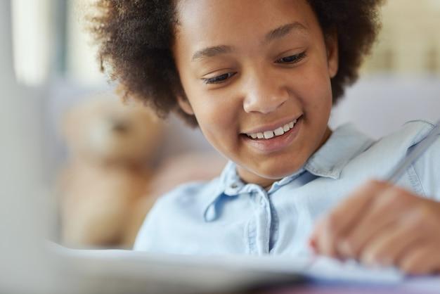 Крупным планом: девушка-подросток смешанной расы выглядит счастливой, делая домашнее задание, проводя время дома
