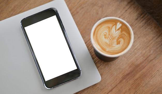 木製の床のラップトップとコーヒーカフェラテハートテクスチャにモックアップの空白の画面のスマートフォンのクローズアップショット