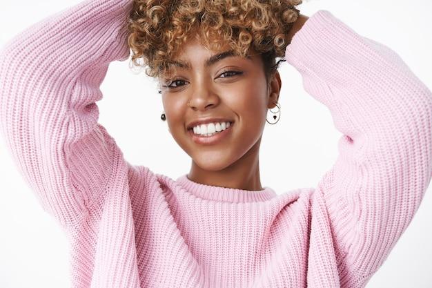 코를 뚫고 귀걸이를 하고 곱슬머리에 손을 잡고 트렌디한 핑크색 스웨터를 입고 즐겁게 웃고 있는 현대적이고 세련된 짙은 피부의 여성의 클로즈업 샷