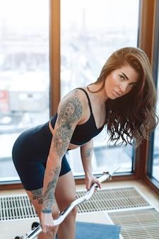근육질의 섹시한 문신을 한 젊은 여성이 역도를 하고 도시 배경에 햇빛이 비치는 체육관에서 카메라를 쳐다보는 사진을 클로즈업합니다.