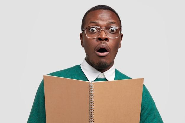 黒人男性のクローズアップショットは、主催者を保持し、愚かな表現をしており、口を大きく開き、眼鏡をかけ、多くを学ぶのが怖い