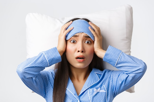 잠자는 마스크와 잠옷을 입고 베개에 누워 불안하고 걱정스러운 표정으로 당황한 아시아 귀여운 소녀의 클로즈업 샷, 뭔가 나쁜 일이 일어났음을 깨닫고, 걱정스러운 흰색 배경