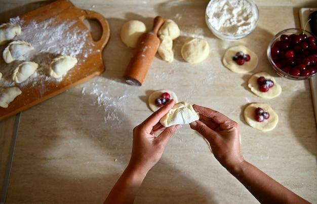 キッチンのカウンタートップの背景に桜の餃子を彫刻するパティシエの手のクローズアップショット。散らばった小麦粉と木の板の上に横たわっている桜餃子。餃子を段階的に調理するプロセス