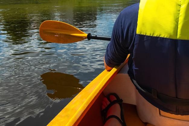 화창한 날에 강에서 카누 사람의 총을 닫습니다.