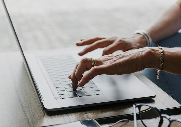 Крупным планом человека, набрав на клавиатуре ноутбука