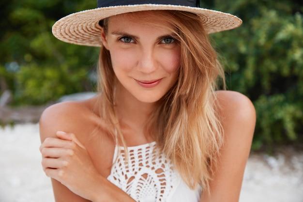 긴 머리를 가진 유쾌한 모습의 클로즈업 샷, 순수한 건강한 피부, 밀짚 모자 착용, 야외 포즈, 연인과 함께 낙원 장소에서 재현, 기쁘게 표현했습니다. 여름 시간과 휴식 개념
