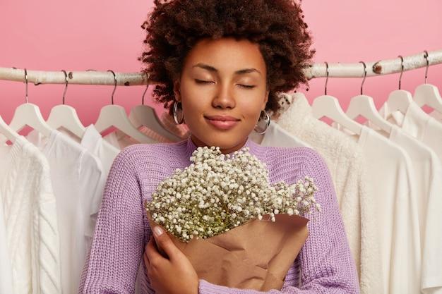 喜んでいる女性のクローズアップショットは美しい花束を保持し、目を閉じて心地よい香りを楽しんで、ラックのワードローブにぶら下がっている服に対してポーズをとる