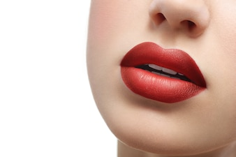 Close up shot of plump sexy female lips covered with lipstick