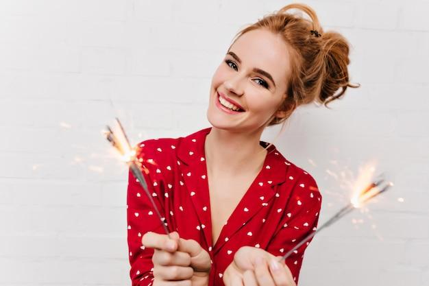 ポジティブな女の子のクローズアップショットは、新年の朝に面白いパジャマを着ています。線香花火を持って白い壁で笑っている魅力的なヨーロッパの女性