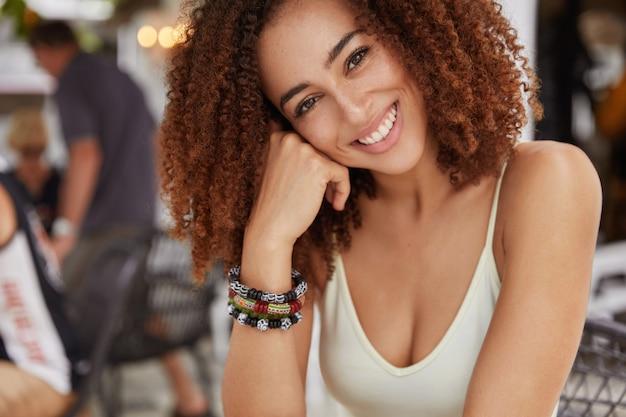 Крупным планом позитивная счастливая женщина с белыми зубами и темными вьющимися волосами