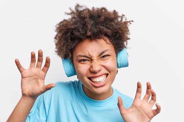 ポジティブな遊び心のあるアフリカ系アメリカ人女性のクローズアップショットは、足を上げ、手を握り締め、歯を食いしばって怒っているふりをします動物は白い壁に隔離された音楽を聴くためのワイヤレスヘッドフォンを着用します