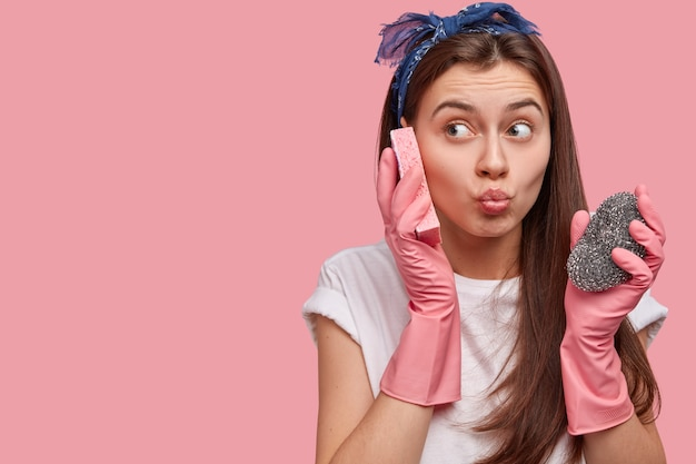 Крупным планом красивая горничная делает гримасу, носит повязку на голову, белую футболку и резиновые защитные перчатки, держит губку возле уха, веселится