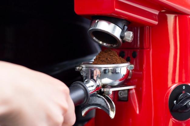 Крупным планом профессиональный бармен готовит кофе эспрессо в эксклюзивном кафе-баре или кафетерии