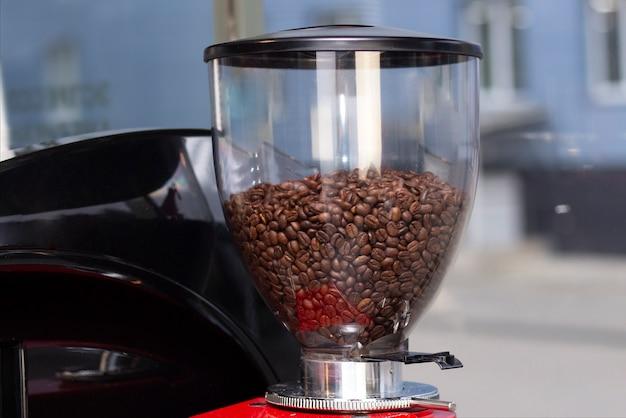 전용 카페 바 또는 카페테리아에서 에스프레소 커피를 준비하는 전문 바텐더의 총을 닫습니다.