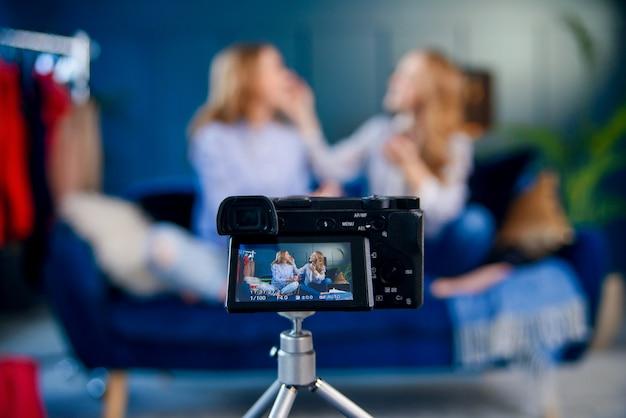 美しさのビデオを記録する2つの魅力的なブロガーの撮影中にプロのカメラのショットを閉じます。