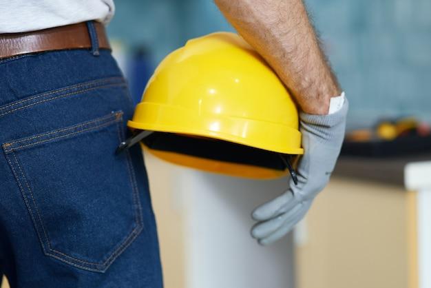 屋内に立っている間ヘルメットを保持しているプロの修理工のショットをクローズアップ