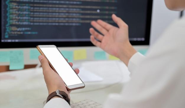空白の画面のスマートフォンを使用してプログラマーの手のクローズアップショット。