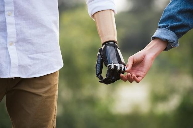 Крупным планом снимок протеза конечности, взявшись за руки с партнершей в нежном прикосновении