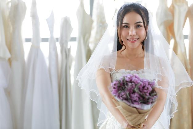 楽屋でぼやけた背景のカメラを見て笑顔で立っているシースルーの髪のベールと白いドレスでアジアの美しい花嫁の手に保持されている紫色の結婚式の花の花束のクローズアップショット。